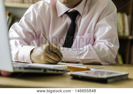 Making some urgent notes. Close-up of man writing something in his note pad while sitting at his working place