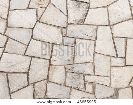 decorative light gray old rough wall made of natural sandstone with potholes and smudges on the street