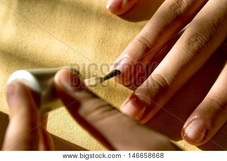 A woman applies a clear coat of fingernail polish to her fingernails.