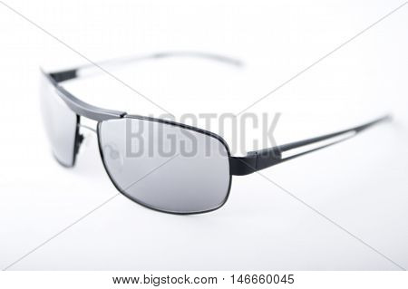 Closeup of black rimmed sunglasses on white background.