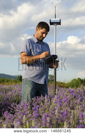 Surveyor working in a lavender field with GPS