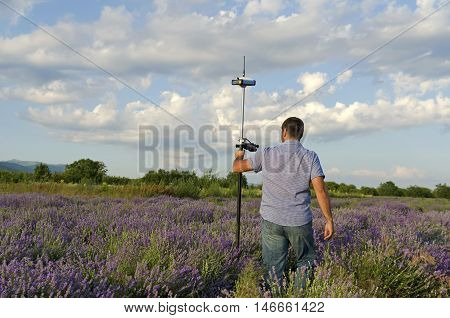 Surveyor walking in a lavender field with controller