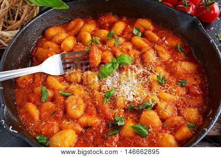 Homemade Italian Gnocchi with marinara sauce, cheese in iron pan.