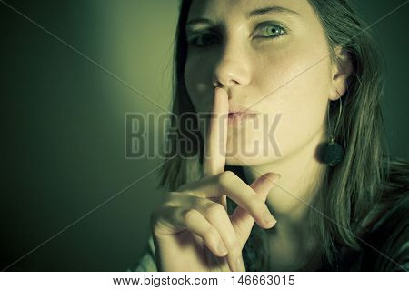 An attractive young woman raises a finger to her lips as if telling someone to keep quiet or indicating that something is a secret. poster