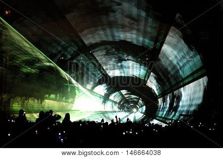 A laser light show at a concert with party goers below and a kaleidescope of colours above. Very futuristic with silhouettes and special light effects. Looks like a tunnel.
