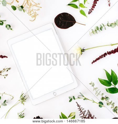 creative decorated and arranged flat lay frame concept with tablet green and purple branches on white background. top view