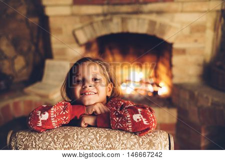 Child in Christmas pajama relaxing by the fire place some cold evening, winter weekends, cozy scene