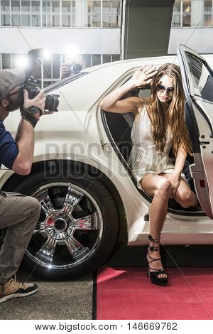 Actress getting out of a limousine on a red carpet event, surroundend by photographers and tabloid paparazzi