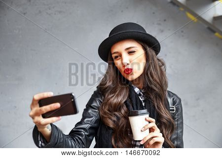Pretty Hipster Girl With Red Lips And In Hat  Taking Selfie And Making Duck Face. Sending Kisses And