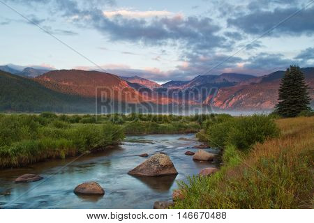 The morning sunlight hits the peaks around Moraine Park as a fog bank rolls over the meadow and The Big Thompson River