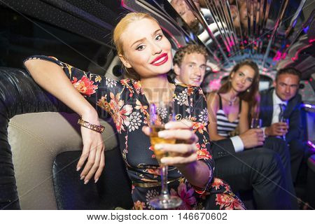 Pretty blonde woman, with glossy red lips holding a glass of champagne, sitting comfortably in a limousine, with a couple of friends in the background