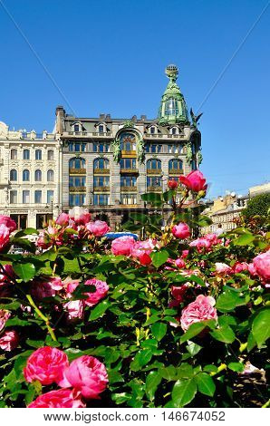 ST PETERSBURG RUSSIA - AUGUST 4 2015. Zinger House on Nevsky Prospect and pink peonies on the foreground. Focus at the building. Architecture landscape in St Petersburg Russia