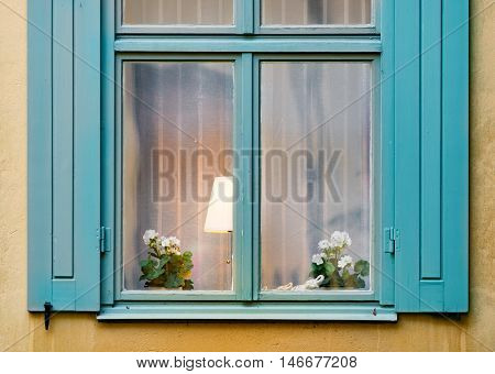 Details of old house window with flower and lamp inside. Yellow wall of building. Stockholm Sweden Scandinavia Europe.