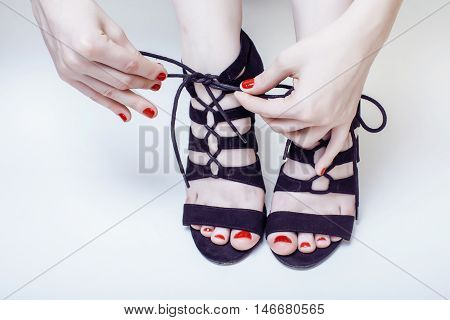 fashion concept people: woman with red nails manicure pedicure tying shoelaces on hight heel shoes isolated on white background, mani pedi together
