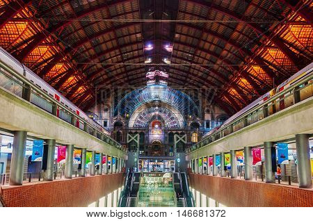 ANTWERP BELGIUM - MARCH 3 2014: Interior of Central railway Station - one of the busiest in the country. Inside located many shops cafes and restaurants. Two trains waiting for passengers