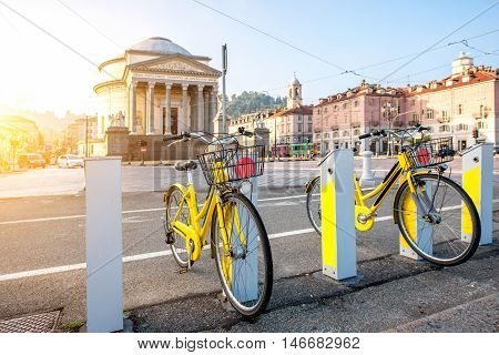 Turin cityscape view on Gran Madre square with church and yellow public bicycles in the morning