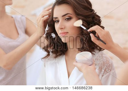 Makeup artist and hairdresser preparing bride before her wedding