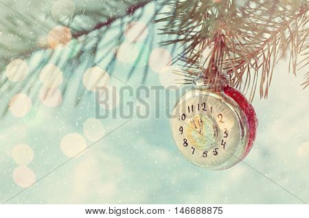 New Year and Christmas background in vintage tones-New Year Christmas toy on snowy fir tree branch. New Year festive card with bokeh. Christmas and New Year background. Focus at the clock.Shallow DOF.
