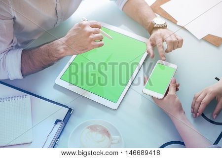 Man and woman working in the office using mockup smartphone and tablet. The view from the top. Clipping path included.