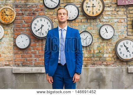 Working in city. Handsome young businessman wearing blue suit and standing with closed eyes against background of brick wall