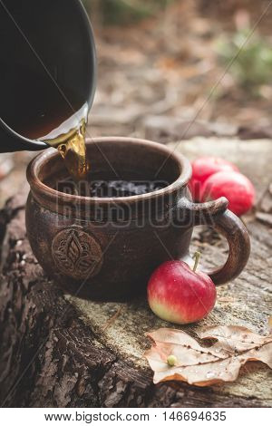 Pouring hot tea in cup and red apples on stub. Fall still life. Selective focus.