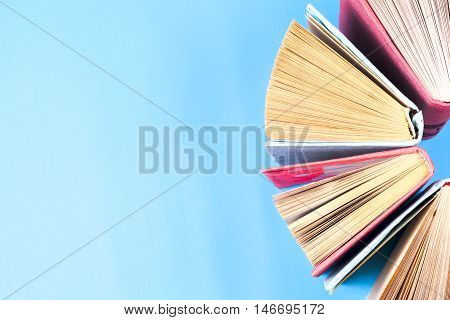 Top view of colorful hardback books in a circle. Open book fanned pages free copy space. Back to school copy space. Education background.