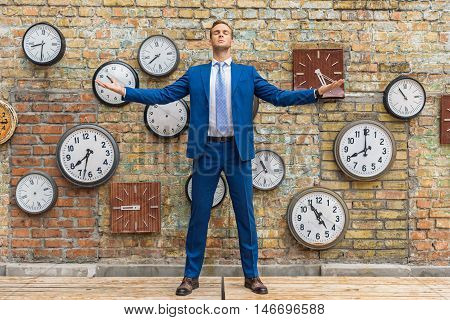 Serious business attitude. Portrait of calm young businessman with closed eyes and his hands raised against of brick wall with clocks