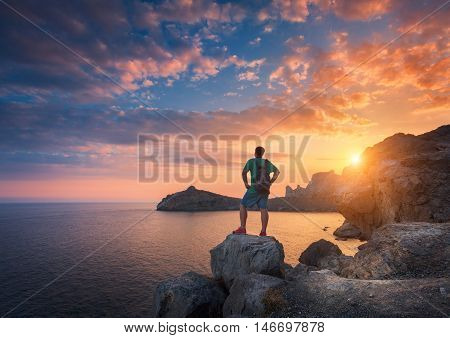Young Standing Man With Backpack On The Stone At Sunset