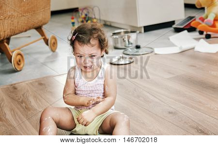 Naughty little child sitting on the floor
