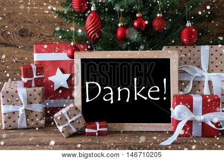 Colorful Christmas Card For Seasons Greetings. Christmas Tree With Balls And Snowflakes. Gifts Or Presents In The Front Of Wooden Background. Chalkboard With German Text Danke Means Thank You