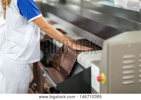 Woman ironing of machines in dry cleaner
