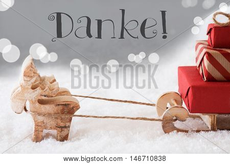 Moose Is Drawing A Sled With Red Gifts Or Presents In Snow. Christmas Card For Seasons Greetings. Silver Background With Bokeh Effect. German Text Danke Means Thank You
