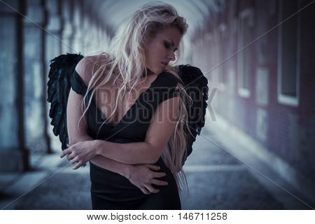 fantasy, an angel in the city, beautiful blonde with long hair dressed in black and with black wings