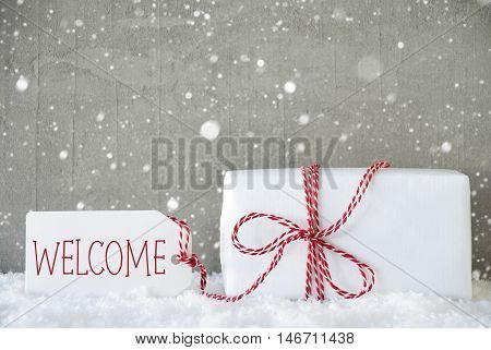 One Christmas Gift Or Present On Snow. Cement Wall As Background With Snowflakes. Modern And Urban Style. Card For Birthday Or Seasons Greetings. Label With English Text Welcome