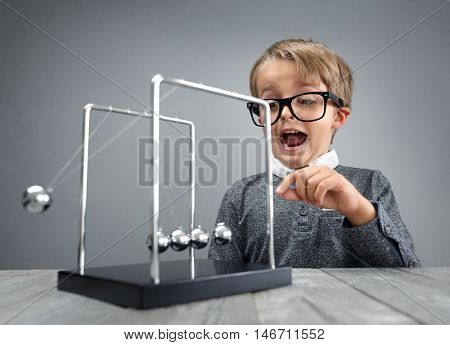 Boy doing experiment with Newton's cradle physics concept for education, action and reaction or cause and effect
