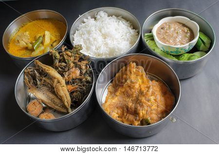 thai food in food carrier thai style,fried fish,chicken curry ,chili saurce,vegetable,stream rice,Thai Omelette,Curried shrimp fried