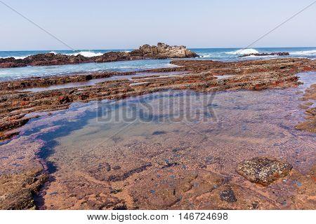 Rocky ocean coastline tidal water pools waves landscape.