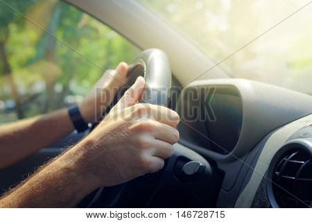 Male hands holding car steering wheel the right way for safe driving