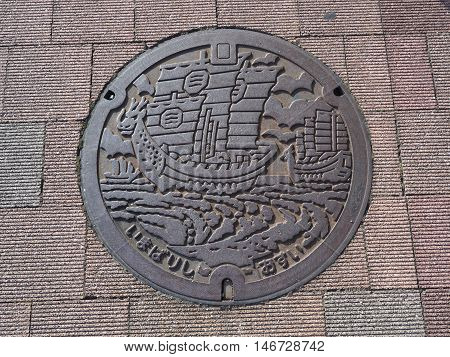 EHIME, JAPAN - JULY 20, 2016: A manhole cover in Imabari, Ehime Prefecture, Japan. The ancient sails were engraved on a manhole cover.
