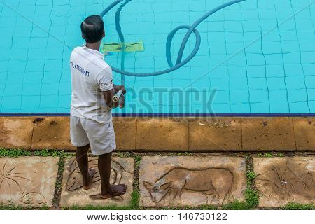 The attendant cleans the pool bottom with a special vacuum cleaner.