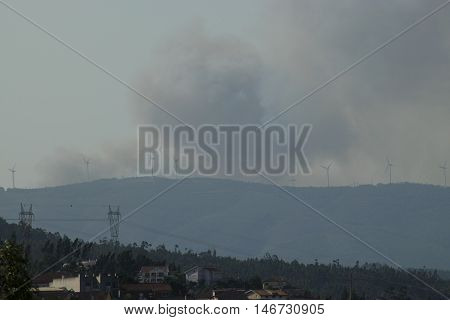 PORTUGAL Coimbra -- 10 Aug 2016 -- Smoke plumes from forest fires just south of the ancient university city of Coimbra Portugal. High temperatures extremely low rainfall and sometimes are the cause of these forest fires. Hundreds of firefighters and aircr