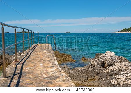 Pathway on the typical rocky beach in Istria, Croatian coast. Blue sea and sky.