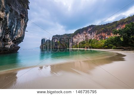 Sandy beach with rocky cliff in the Andaman sea, Thailand