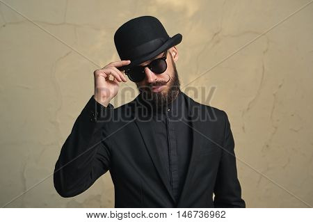 Bearded Man with black Clothes greets. Fashion Portrait