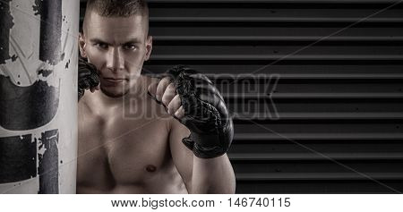 mma fighter in fighing stance near punching bag