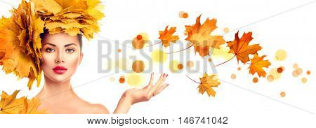 Autumn Woman, Fall. Beauty model girl with autumn bright leaves hairstyle. Beautiful Brunette Girl showing empty copy space on open hand palm for text. Proposing a product. Gestures for advertisement