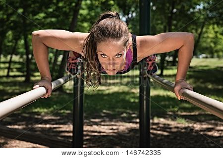 Female athlete exercising on parallel bars doing push-ups