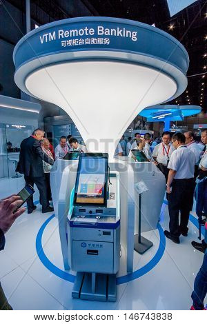 SHANGHAI CHINA - AUGUST 31 2016: Attendees look at VTM Remote Banking appliance at Huawei Connect 2016 information technology conference and exhibition in Shanghai China on August 31 2016.