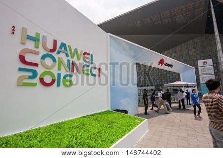 SHANGHAI CHINA - SEPTEMBER 2 2016: Attendees of Huawei Connect 2016 IT conference near entrance to World Expo Exhibition and Convention Center in Shanghai China on September 2 2016.