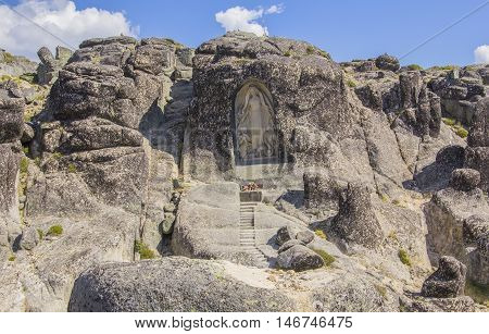 background view of a small chapel with a bas-relief  in the rocks in the nature reserve of Sierra de Eshtrella in Portugal
